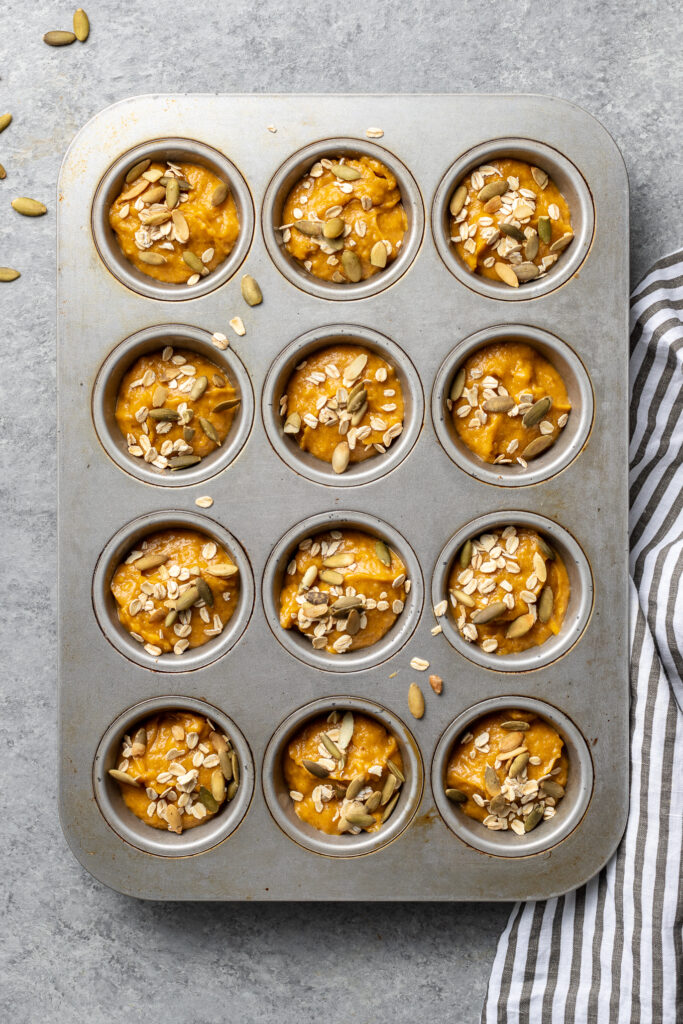 A muffin tin filled with batter for a batch of pumpkin muffins.