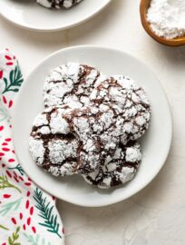 Small white plate filled with chocolate crinkle cookies.