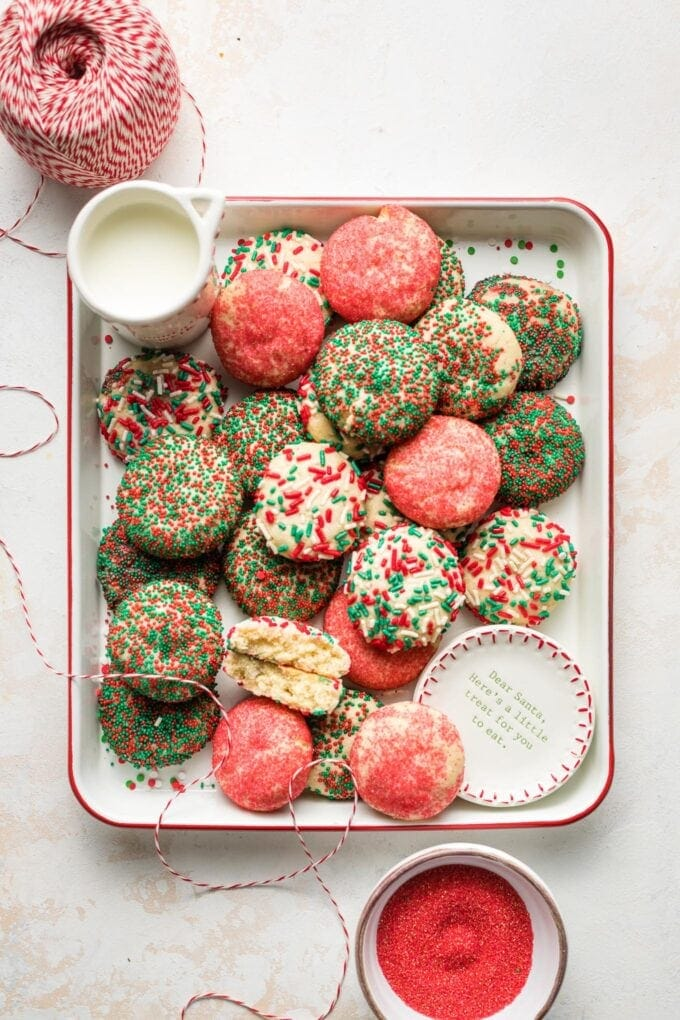 Tray holding sprinkle sugar cookies set out with milk for Santa.