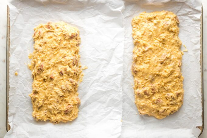 Two logs of cookie dough shaped into mounds for baking biscotti.