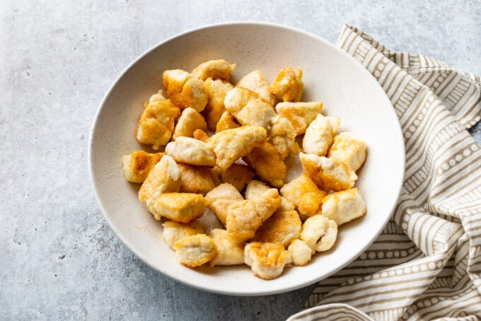 Chicken pieces with perfect brown edges set aside in a bowl.