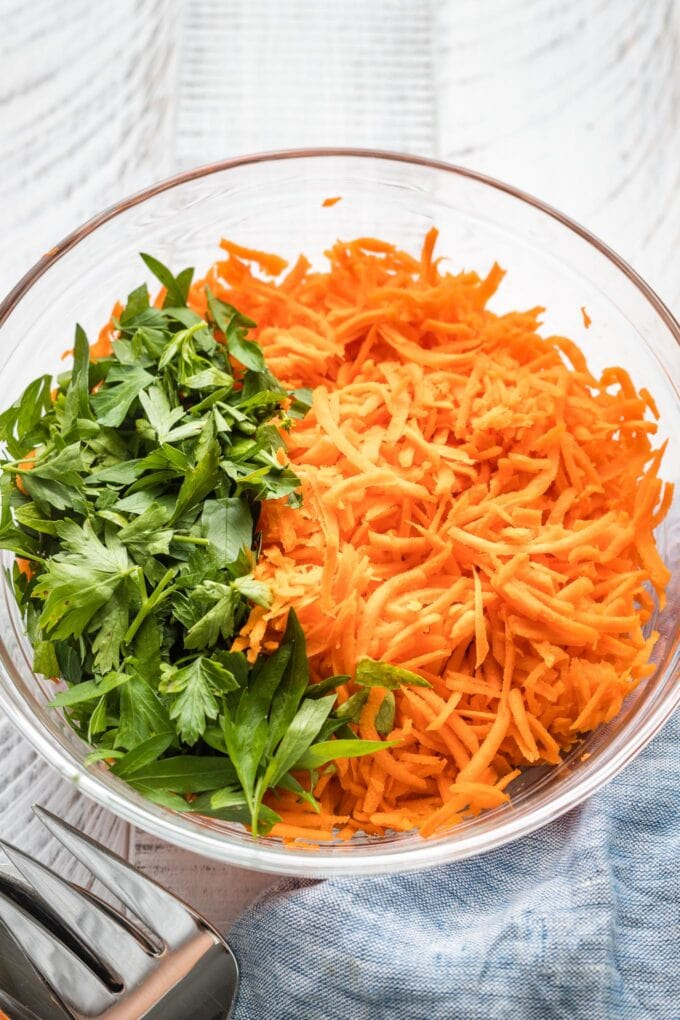 Close up of shredded carrots and chopped parsley in a clear prep bowl.