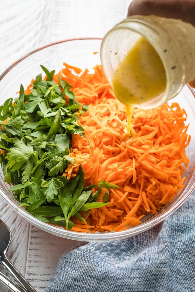Salad dressing being poured onto a grated carrot salad.