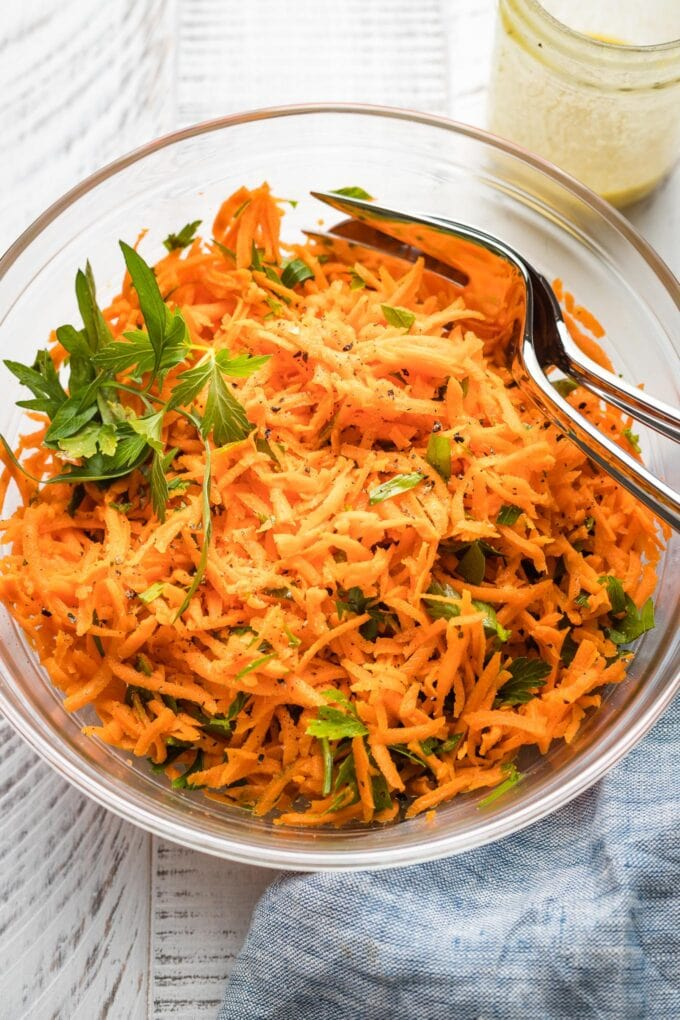 Clear glass bowl holding a French carrot salad.