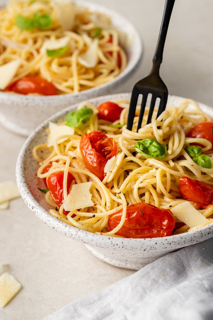 A bowl of pasta with a fork twirled around a big bite.