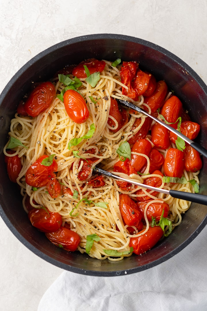 Large pot filled with roasted tomato and garlic spaghetti, ready to serve up.