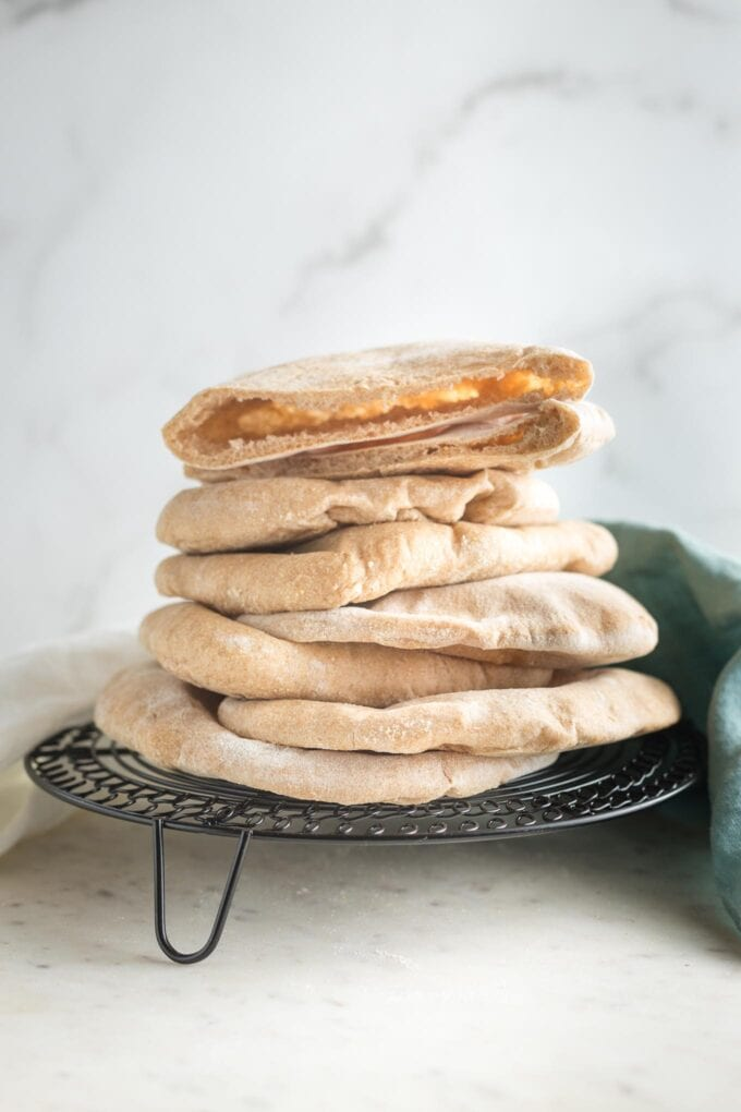 Stack of homemade whole wheat pita bread on a cooling rack.