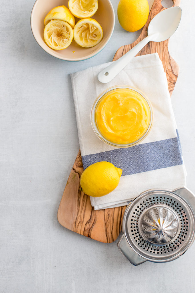A jar full of bright yellow homemade lemon curd on a white and light blue dishcloth.