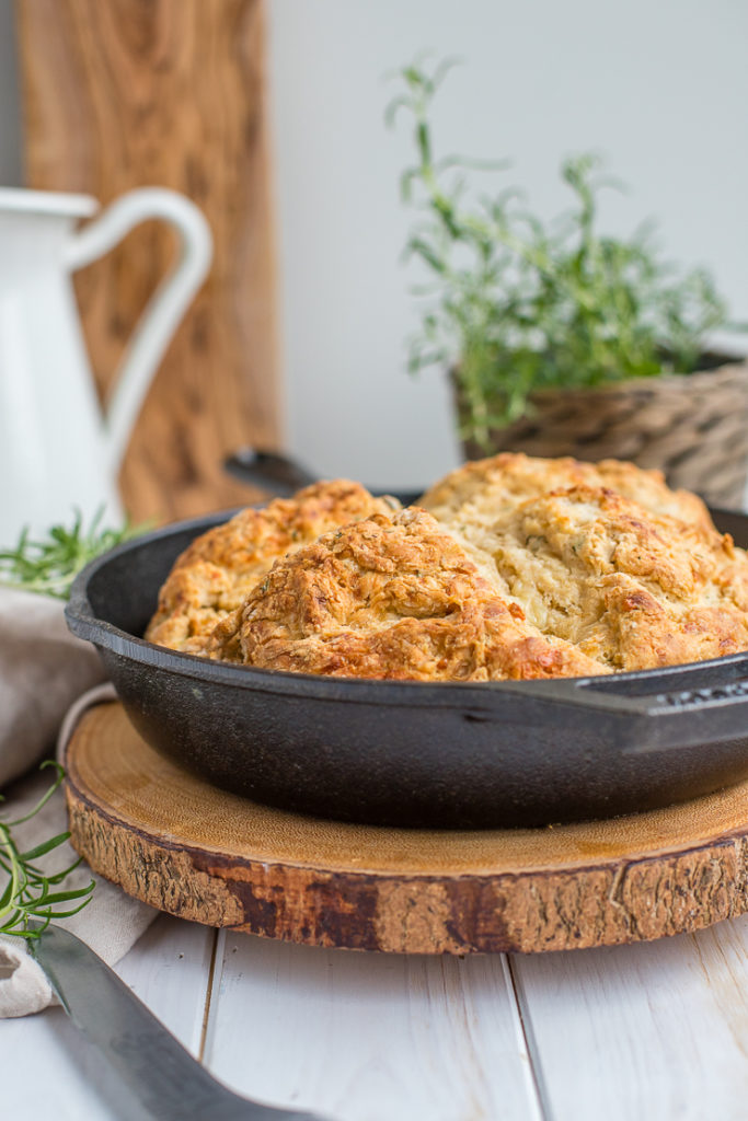A side-view of savory soda bread baked in a cast-iron skillet, cooling on the counter.