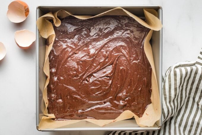 Raw brownie batter spread in a 9x9 pan.