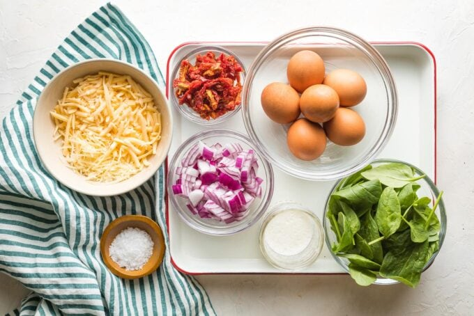 Prep bowls holding eggs, spinach, Parmesan and Gouda cheese, chopped red onion, sun-dried tomatoes, cream, salt and pepper.
