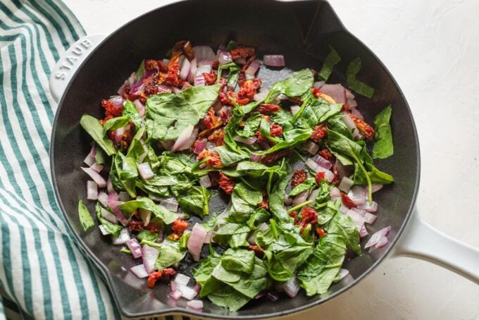 Spinach, onion, and sun-dried tomato sauteed in a skillet.