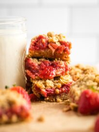 Close-up of three stacked strawberry rhubarb crumble bars.
