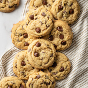 Pile of soft chocolate chip cookies on top of a napkin, with a glass of milk to the side.