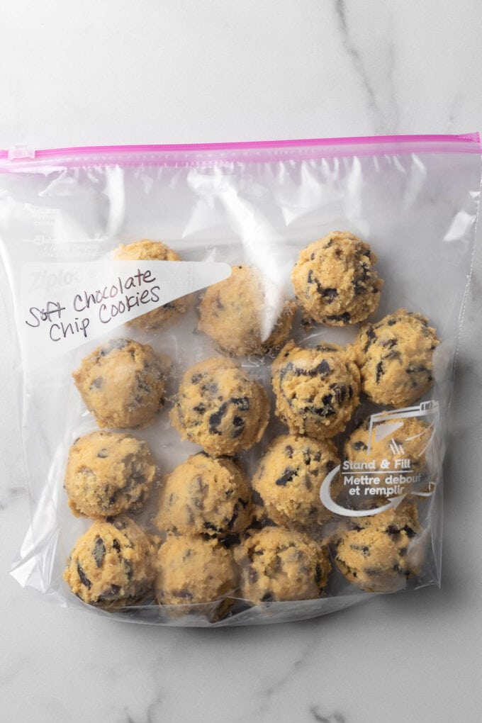 Chocolate chip cookie dough balls in a freezer-safe bag, ready to store.