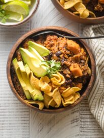 Bowl of sweet potato black bean chili served with avocado, cilantro, and corn chips.
