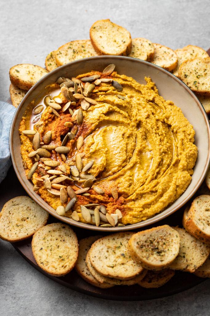 Bowl of pumpkin hummus with pumpkin seeds and paprika.
