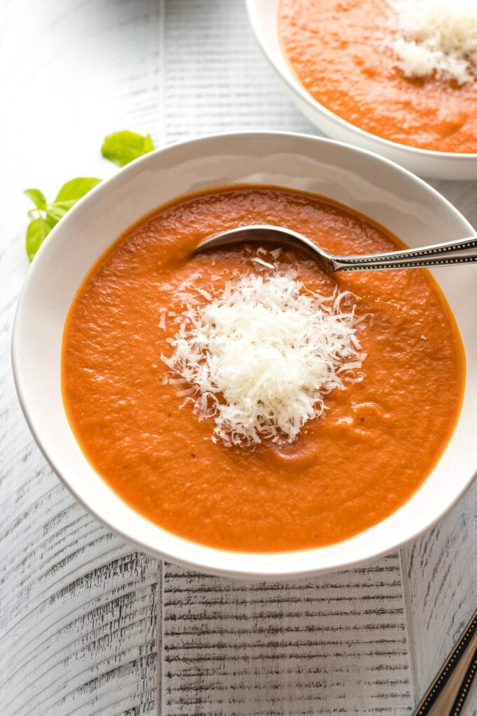 Bowls of creamy roasted tomato basil soup, garnished with Parmesan cheese.