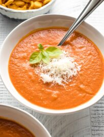 Bowls of creamy roasted tomato basil soup, garnished with fresh basil and Parmesan cheese, served with Goldfish crackers.