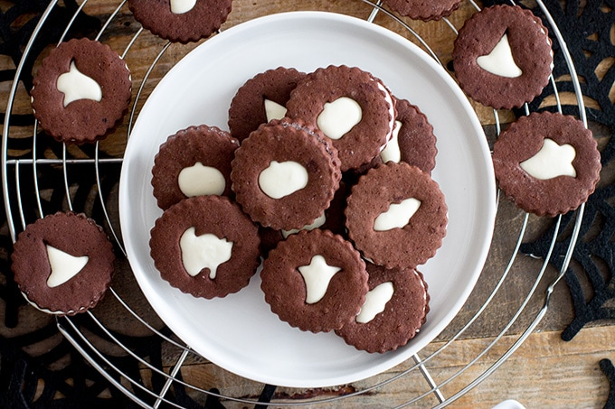 Spooky chocolate Linzer cookies | Dark chocolate sugar cookies sandwiched with an easy marshmallow cream frosting, with spooky cut-outs for a Halloween treat! #halloween #chocolatesugarcookies