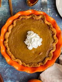 Overhead picture of a whole bourbon molasses-spiked pumpkin pie with a large dollop of whipped cream.