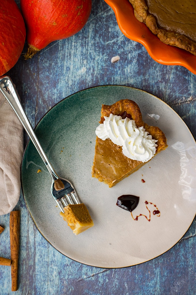 A slice of bourbon molasses-spiked pumpkin pie with whipped cream.