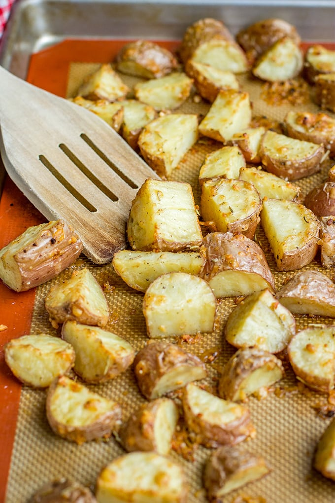 Close-up of parmesan herb crusted red potatoes, roasted on a baking sheet.