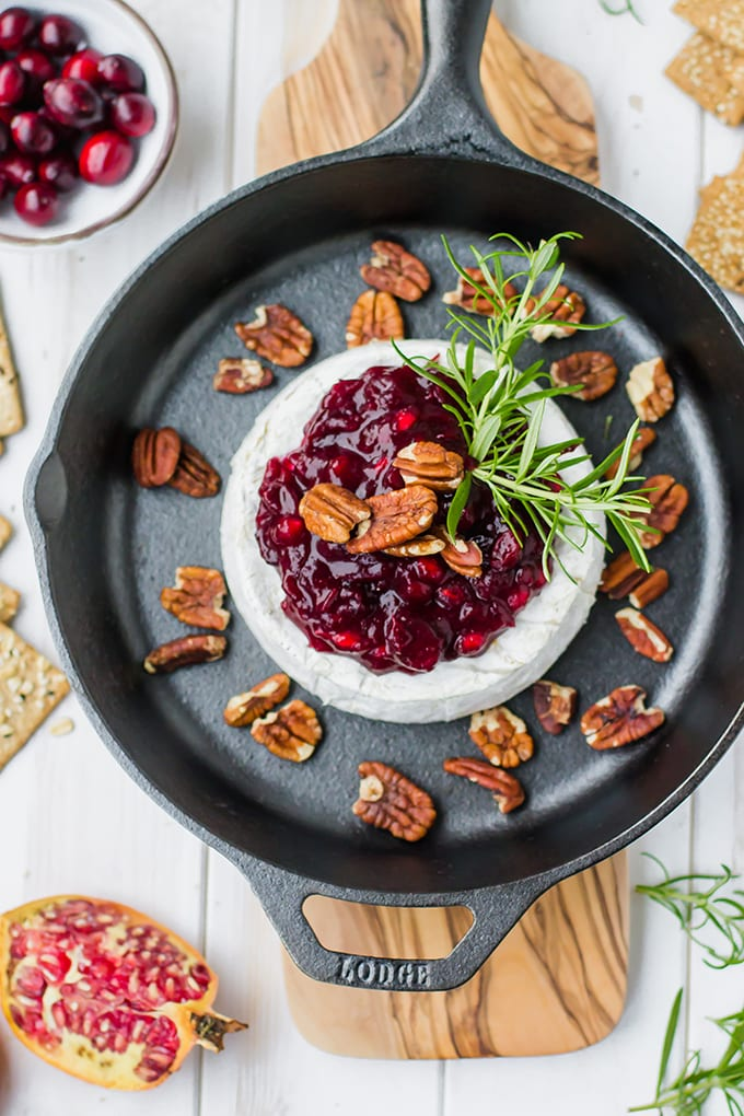 A large wheel of brie baked in a cast-iron skillet, topped with cranberry pomegranate sauce, pecans, and fresh rosemary.