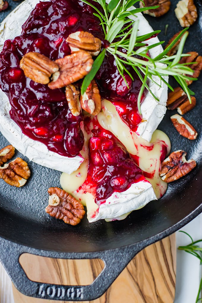 A large wheel of brie baked in a cast-iron skillet, topped with cranberry pomegranate sauce, pecans, and fresh rosemary, with a wedge partially removed.
