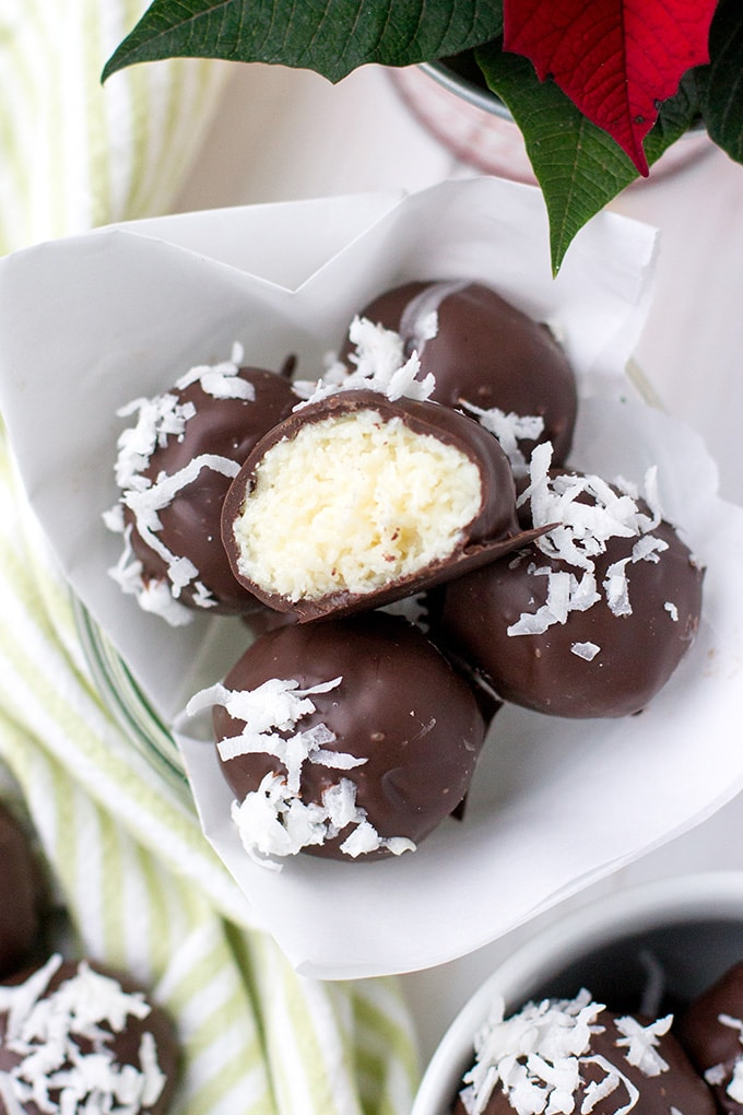 Close-up image of dark chocolate coconut truffles, with one lying on top with a bite out of half.