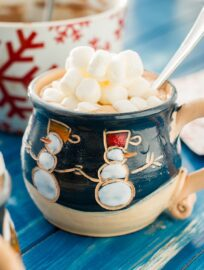 A mug full of classic hot cocoa topped with mini marshmallows.