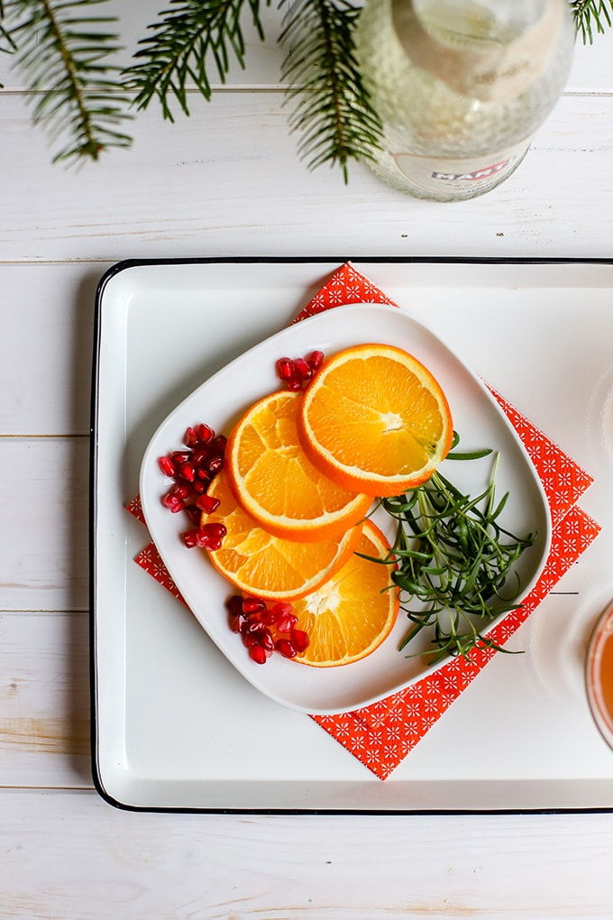 A small square white plate holding garnishes for orange pomegranate Prosecco cocktails.