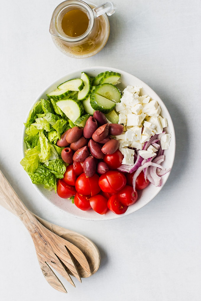 Overhead picture of a simple Greek salad with romaine lettuce, cherry tomatoes, kalamata olives, cucumber, red onion, and feta cheese.