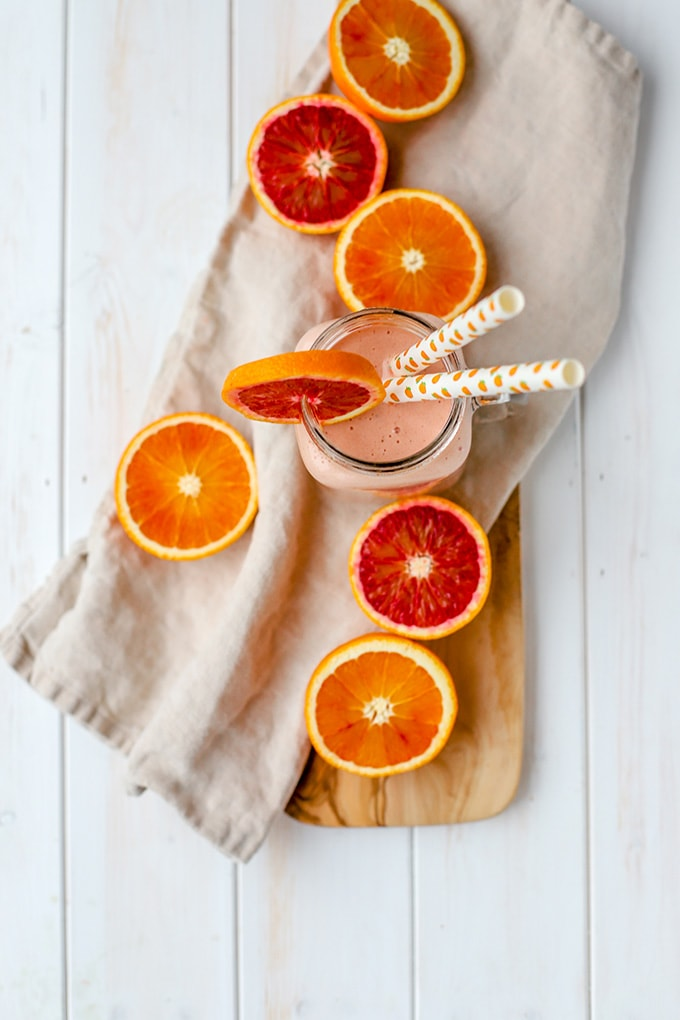 Flat-lay photo of a blood orange banana smoothie, surrounded by bright orange and red slices of citrus.