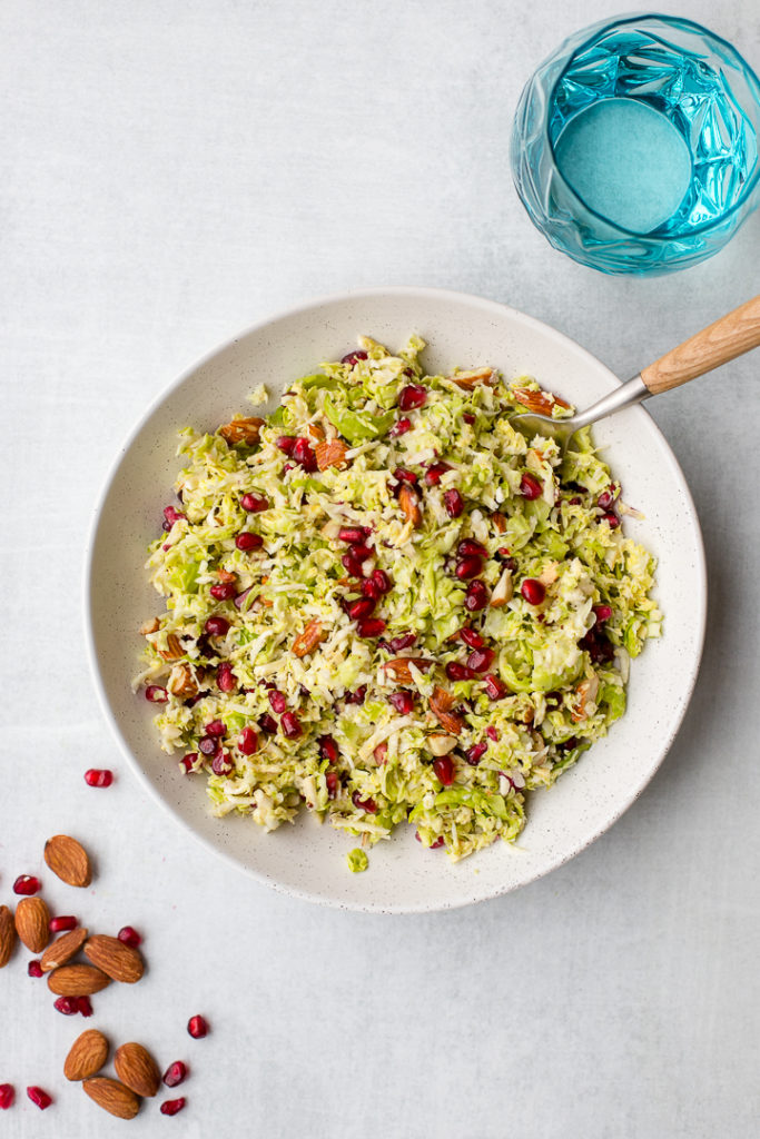 A serving dish filled with shaved brussels sprouts pomegranate salad.