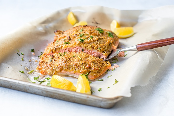 Serving a portion of mustard-crusted panko salmon.
