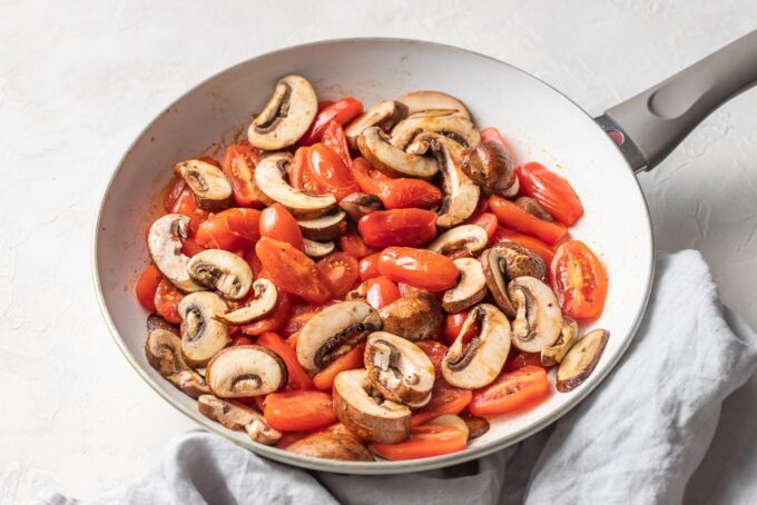 Tomatoes and sliced mushrooms in a skillet.