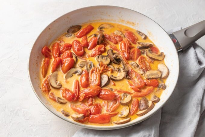 Tomatoes and mushrooms cooking in a broth and white-wine sauce.