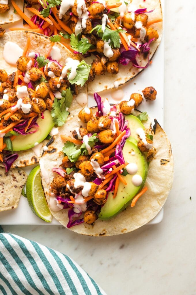 Crispy chickpea tacos with sunset slaw and a creamy sauce arranged on a serving tray.
