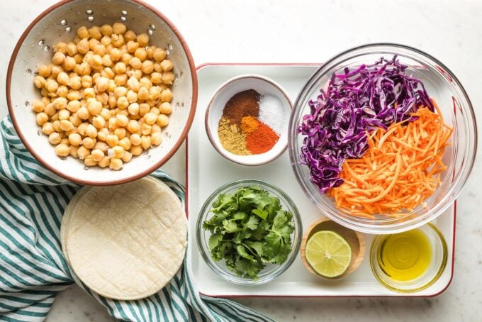 Prep bowls filled with rinsed chickpeas, red cabbage, shredded carrots, seasonings, cilantro, lime, olive oil, and tortillas.