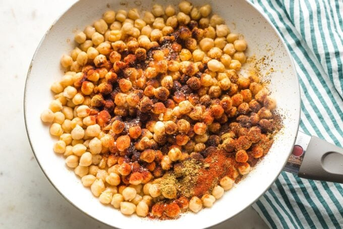 Chickpeas in a skillet with seasoning sprinkled on top.