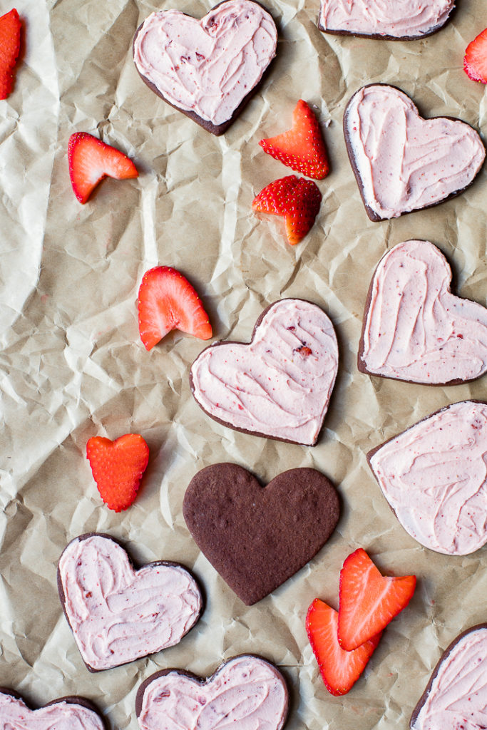 Heart-shaped strawberry-frosted chocolate sugar cookies, scattered with freshly-cut strawberries on crinkled parchment paper.