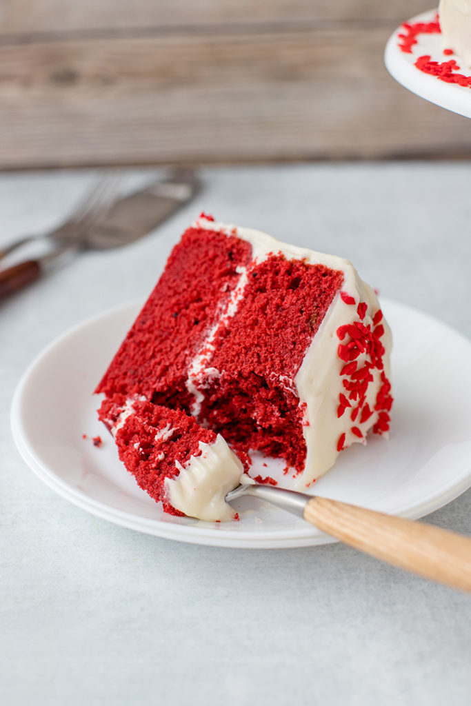 A slice of red velvet cake with a generous forkful removed.