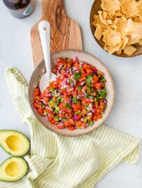 A bowl full of homemade pico de gallo, with chips, avocado, and a cold beer.