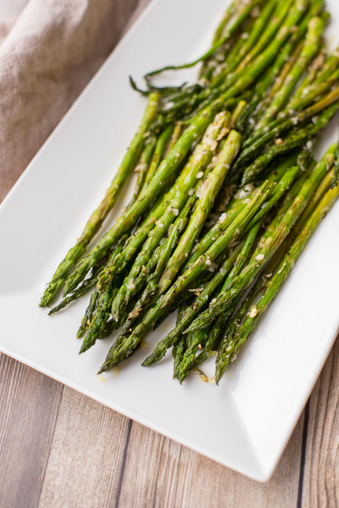 Roasted lemon pepper asparagus plated on a rectangular white tray.