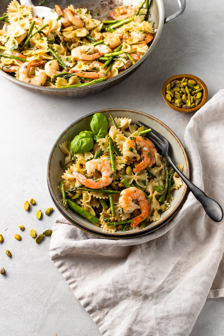 A small bowl filled with a generous serving of lemon asparagus pasta, topped with shrimp and garnished with fresh basil.