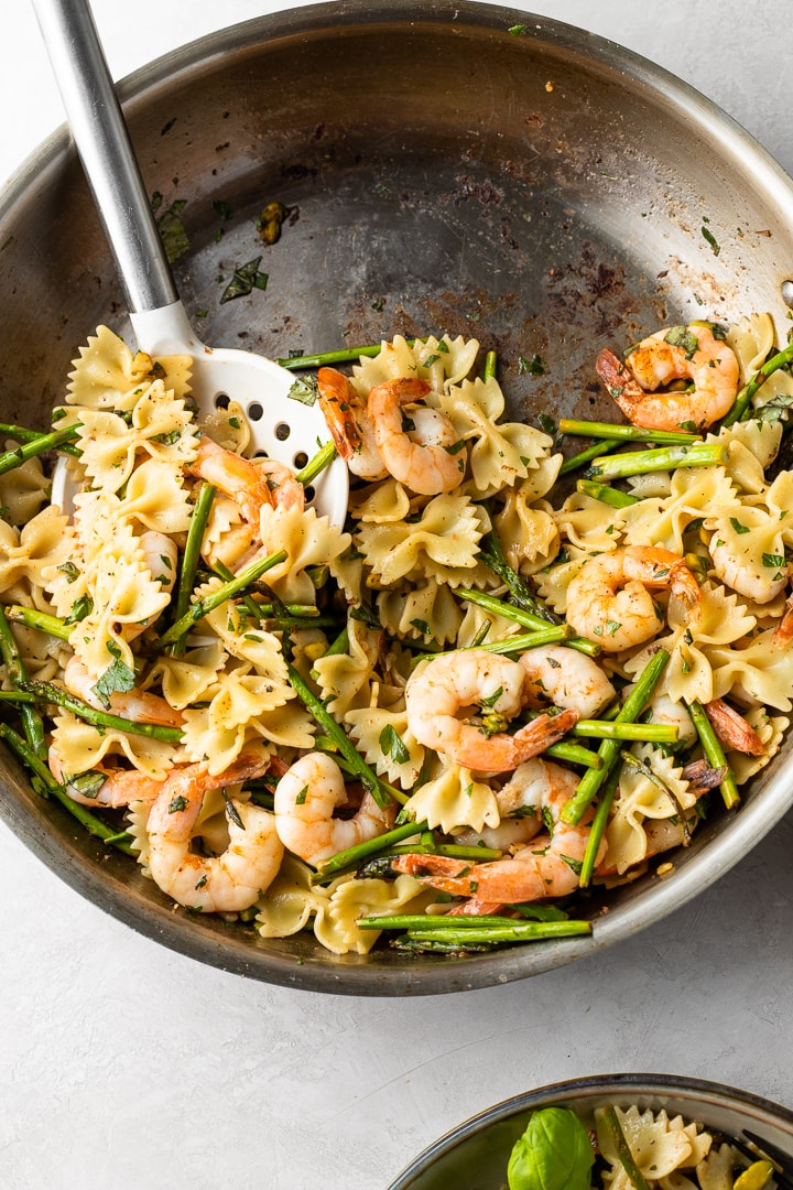 Skillet filled with lemon asparagus shrimp pasta.