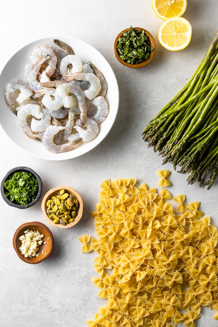 Flat lay of raw shrimp, lemons, herbs, spices, asparagus, and farfalle (bowtie) pasta.