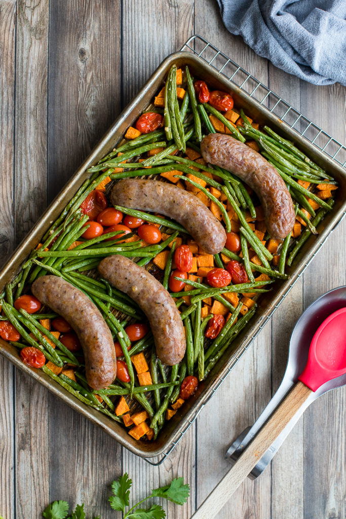 Flat-lay of an Italian sausage sheet pan dinner with sweet potatoes, green beans, and cherry tomatoes, resting on a cooling rack with a red serving spoon to the side.