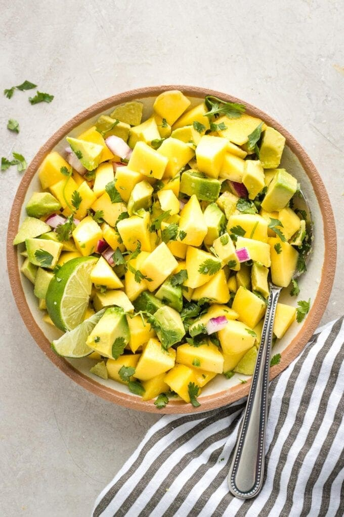 Close up of mango avocado salsa in a bowl with a spoon.
